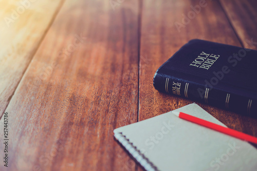 Fotografia  Holy bible with note book and pencil on wooden table against morning  sun light