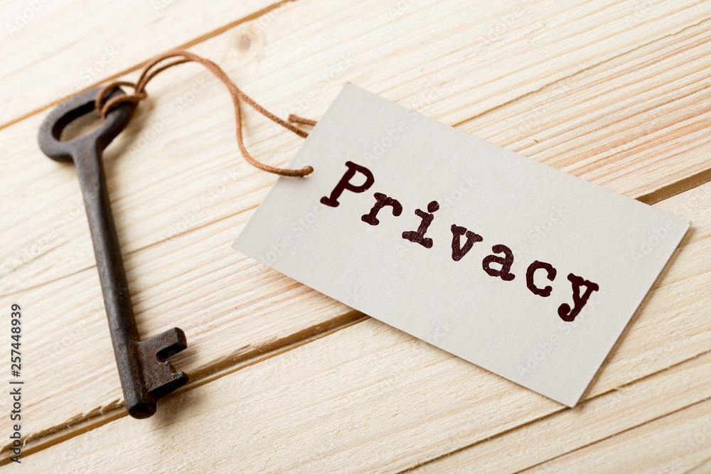 Fototapeta privacy concept - little house and key with inscription on the wooden desk