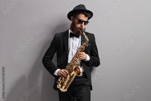 Fototapeta Man playing a sax and leaning against gray wall