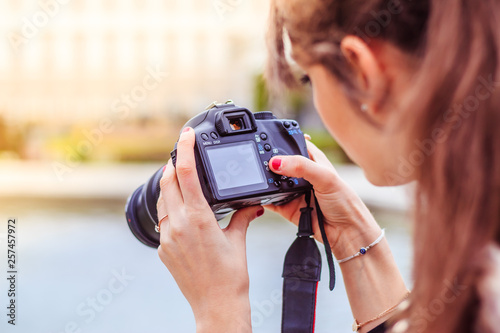 Fototapeta Young female tourist girl is taking shots with her camera obraz na płótnie