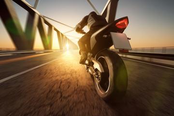 Motocykl jedzie przez most na zachodzie słońca