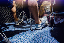 Man Put White Sport Shoes And Playing The Drum Set And Bass Drum With Foot In Music Room