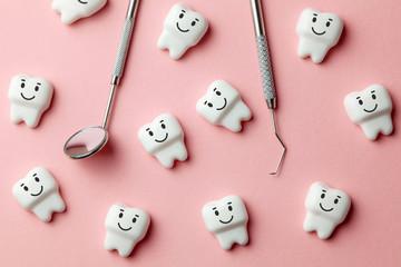 Zdrowe białe zęby uśmiechają się na różowym tle i dentysta narzędzia lustro, hak.