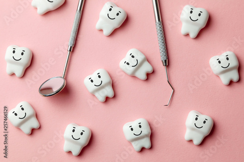fototapeta na lodówkę Healthy white teeth are smiling on pink background and dentist tools mirror, hook.