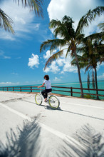 Anna Carradice-French Rides A Beach Cruiser Bicycle Down A Bridge In Key West, Florida.