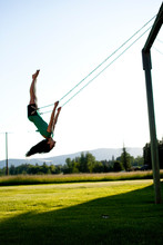 A Young Women Swinging Smiles While Looking Back On A Summer Evening In Idaho.
