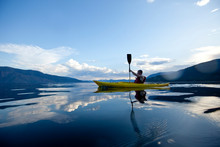 Young Man Paddles Yellow Kayak On Lake Pend Oreille In Sandpoint, Idaho.