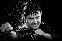A Young Man Wearing A Jacket Poses In A Wushu Stance While It Rains Down On Him On March 20, 2009.