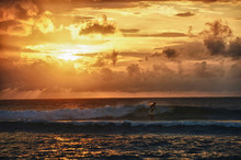 Surfer Riding A Small Wave At Sunset