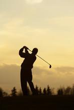 A Golfer At Tees Off At Sunset.