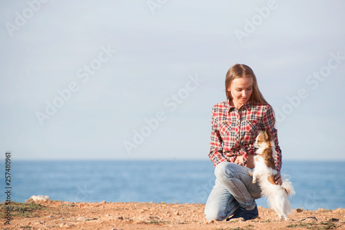 Fotografia  happy smiling young caucasian female in plaid shirt and jeans with her small pet