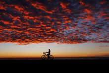 Woman Riding Bike Along Silhouette Horizon, La Jolla, San Diego, California, USA