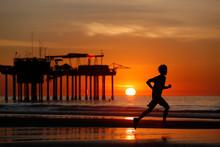 Silhouette Of Runner At Sunset On Beach