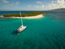 A Catamaran Rests In The Clear...