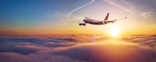 Commercial Airplane Flying Over Dramatic Sunset