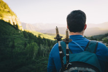 A Young Man Looks Over A Mountain Valley With Trekking Poles On His Back.