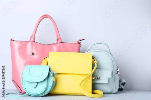 Fototapeta Fashion handbags and backpack on grey background
