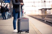 Pretty Young Woman With Smal Hand Luggage Waiting At The Traint Station For Her Train, Transportation Concept