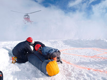 Mountain Rescuers Are Protecting A Victim For The Down Wind Of The Landing Helicopter At 14.000 Foot On Denali, Formerly Known As Mount McKinley.