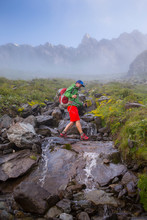 A Solo Male Hiker Is Crossing A Mountain Stream In The Swiss Alps. Early Morning Mist Is Rising.