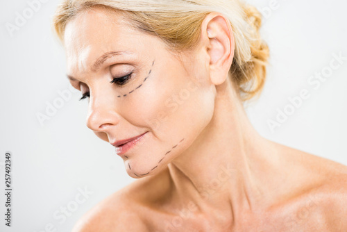 Fototapeta  beautiful and middle aged woman with lines on face looking down on grey backgrou