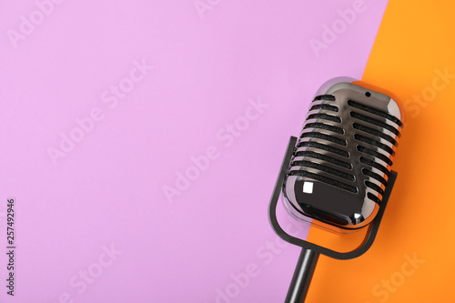 Fotografia Retro microphone on color background, top view with space for text