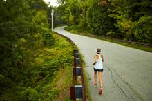A Woman Runs Up A Hill Along A...