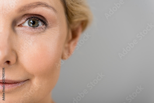 Stampa su Tela  selective focus of mature woman looking at camera isolated on grey