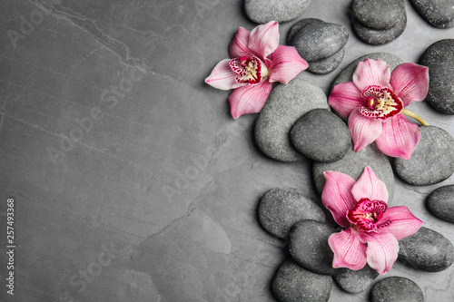 Stampa su Tela Zen stones and exotic flowers on dark background, top view with space for text