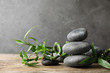 Stacked zen stones and bamboo on table against grey background. Space for text