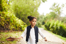 Girl With Brown Leaf In Country Road