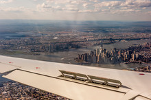 Aerial View Of New York City From An Airplane Looking Over The Wing Showing Lower Manhattan, And New Jersey.