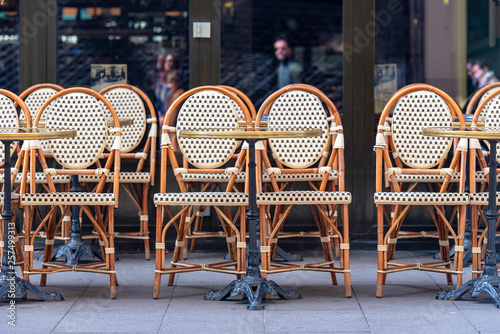 Obraz Rows of traditional Chairs of a Street Cafe in France, french furniture in a Street  - fototapety do salonu
