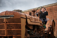 Boy Sitting On Old Tractor