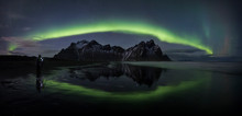 Photographer Under Full Arc Of Aurora Borealis, Vestrahorn, Iceland
