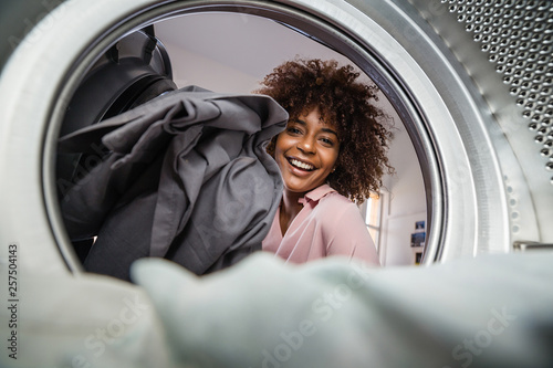 Fotografie, Obraz Young black African American woman holding a basket of clothes to be washed in a