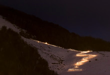 Skiers At Night Carry Torch And Ski Down A Trail At Cerro Catedral In Argentina