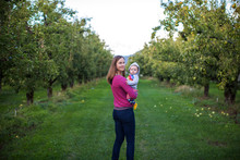 Mother Holding Baby Son In Orchard