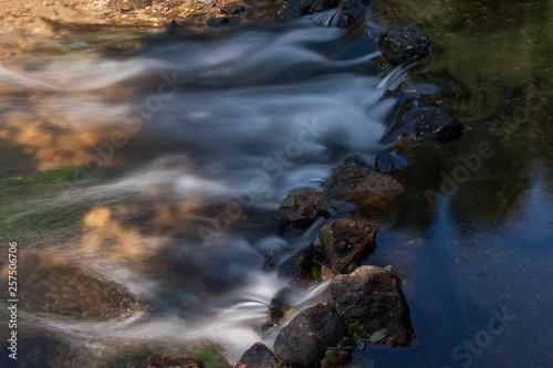 Valokuvatapetti Água cristalina que, flui por entre as pedras de uma pequena represa construída pelo Homem, formando pequenas cascatas