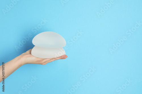 Woman holding silicone implants for breast augmentation on color background, space for text Wallpaper Mural