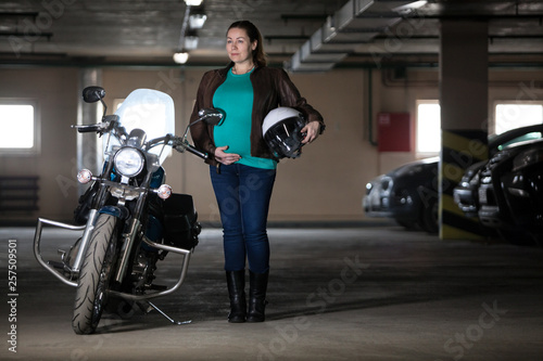 Portrait of pregnant woman biker standing next to motorcycle with white helmet in hand, underground garage