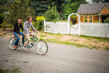 A Newly Married Couple Riding Tandem Bicycle