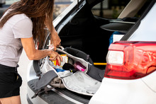 Woman Packing Bag In Trunk Of ...