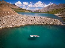 Woman Lying On Paddle Board On Lake In Colorado, USA