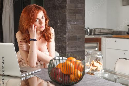 Fototapeta bella ragazza usa il computer mentre fa colazione in casa