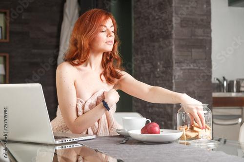 Fotografie, Obraz bella ragazza usa il computer mentre fa colazione in casa