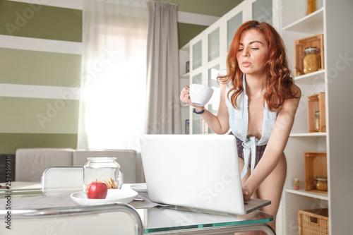 bella ragazza usa il computer mentre fa una veloce colazione фототапет