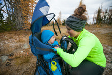 Side View Of Mother Buckling Baby Into Hiking Backpack