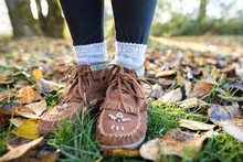 Moccasin Shoes On Legs Of Woman In Park