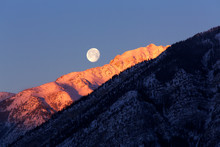 A Full Moon Over A Snow Covered Mountain Top In Banff National Park, Alberta, Canada.